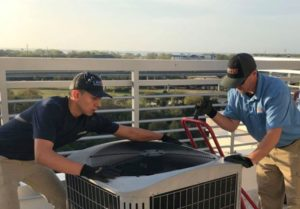Our junior technician performing a routine heat pump maintenance for a client in Charleston